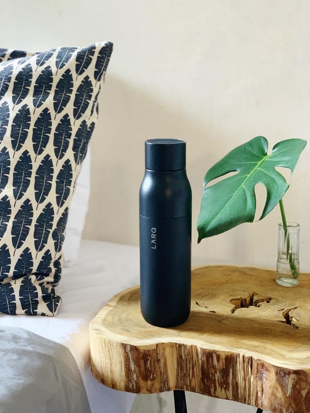 black Larq insulated bottle on wood slice table