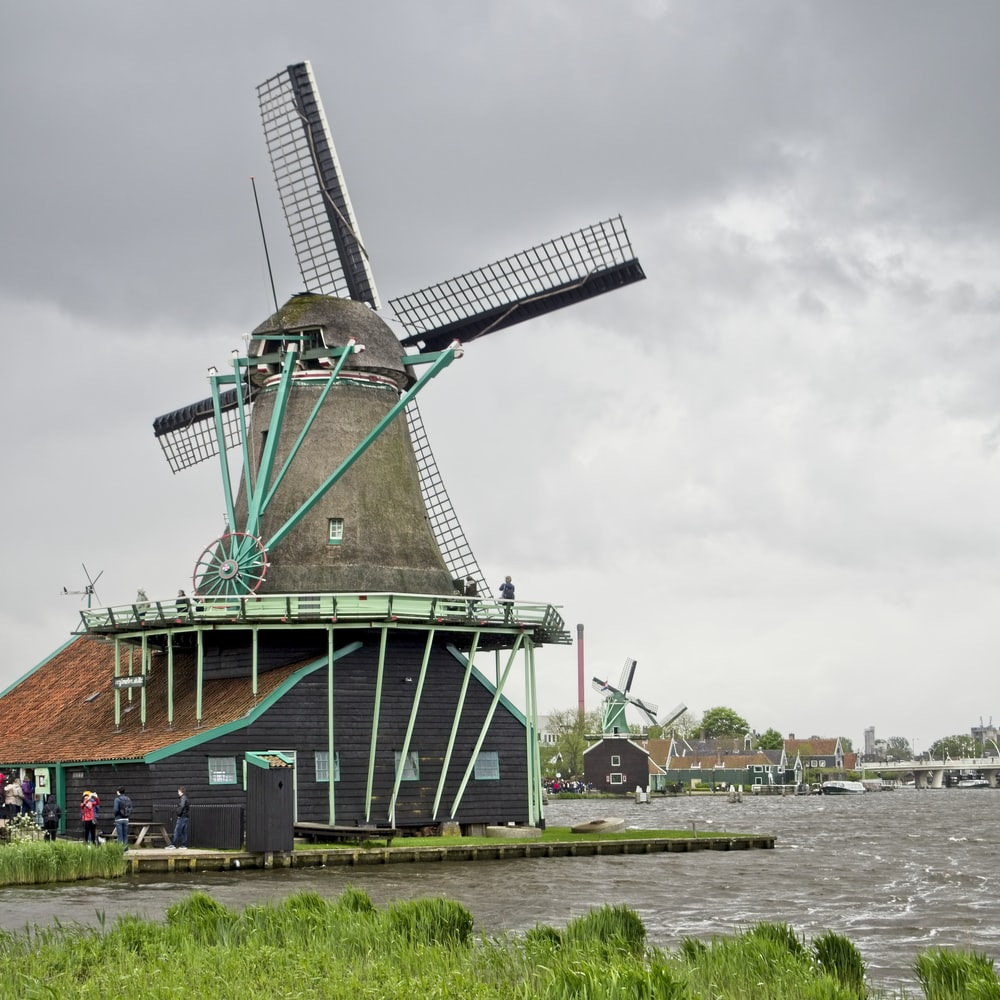 gray and brown windmill beside body of water