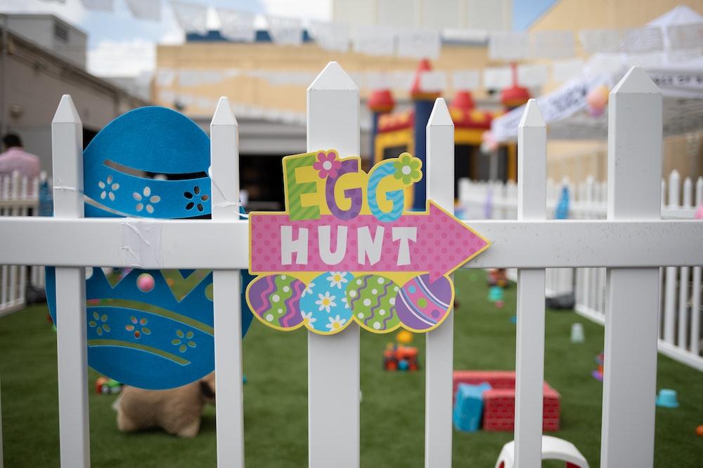 multicolored egg hunt decor on white wooden fence
