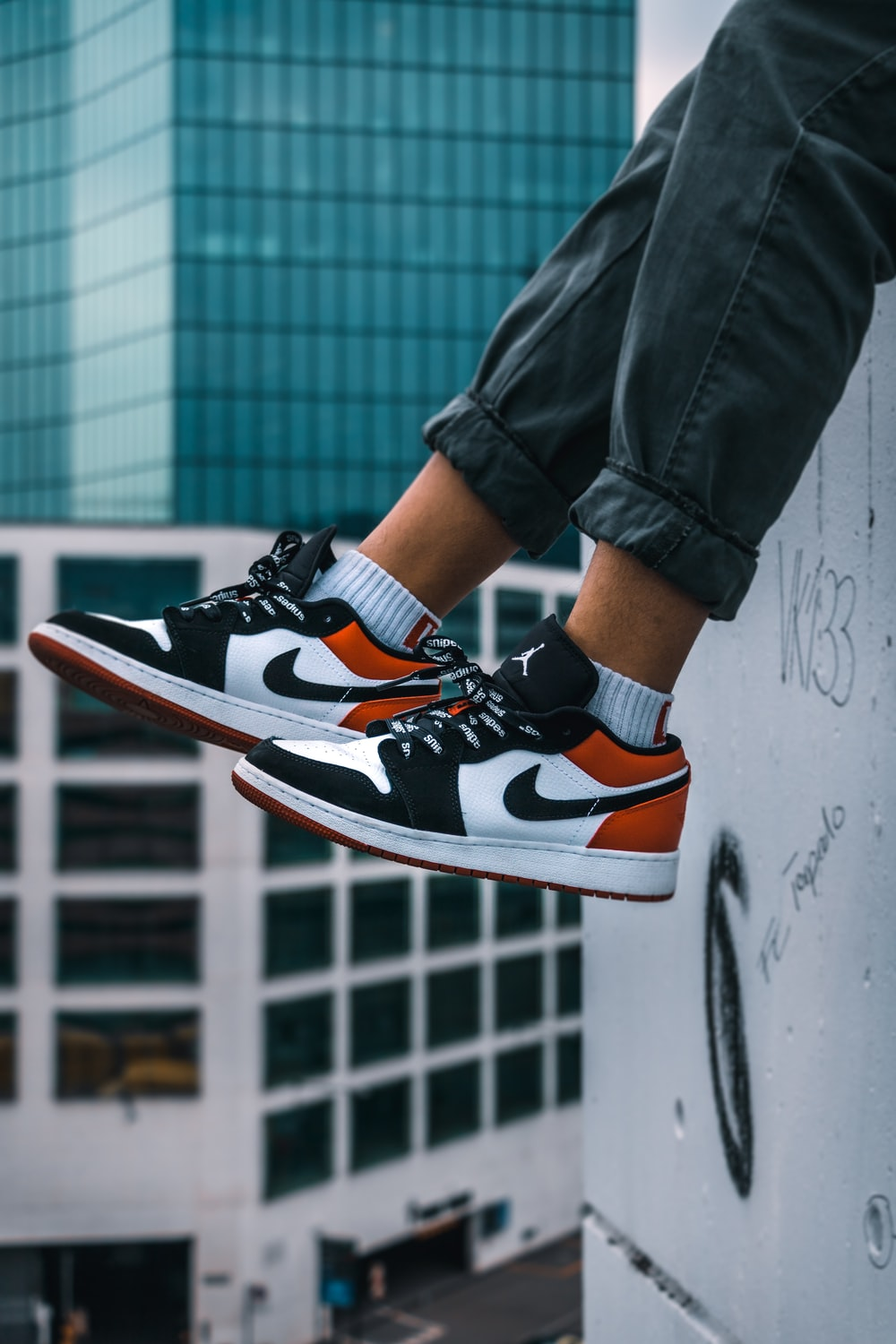 man sitting on the ledge of a building wearing Air Jordan 1 low-top shoes