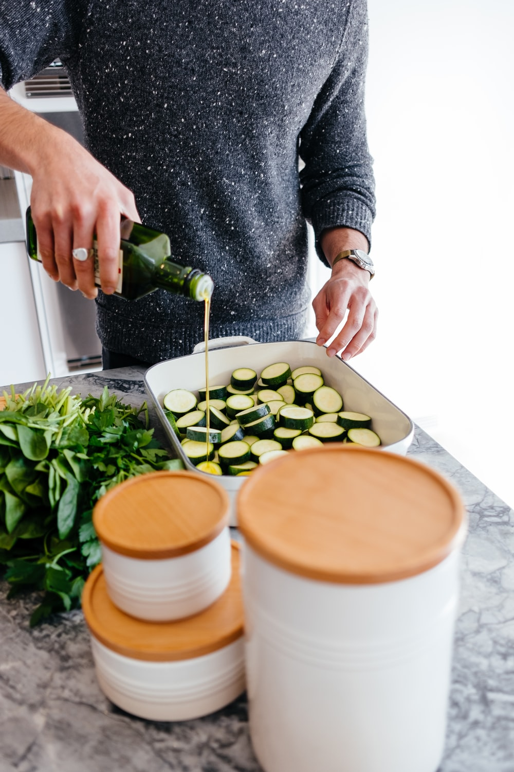person standing and putting oil on sliced zucchini