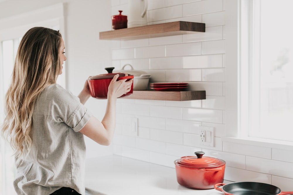 woman holding red cookware