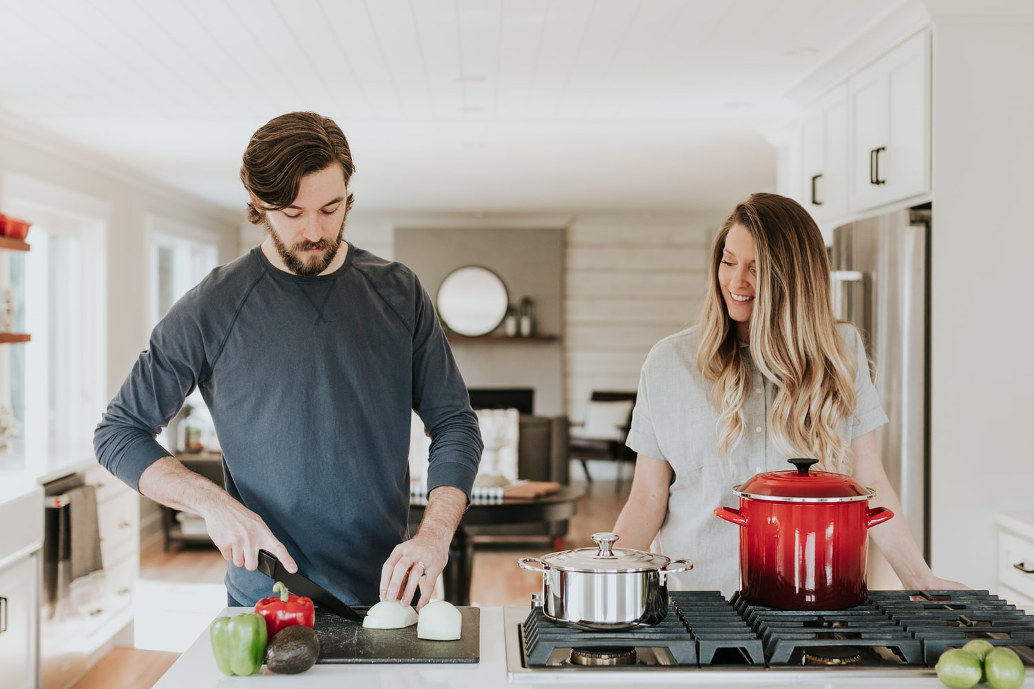 couples in the kitchen while the man is cutting