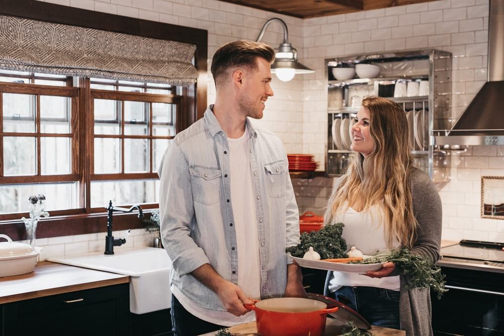 man and woman standing inside kitchen room