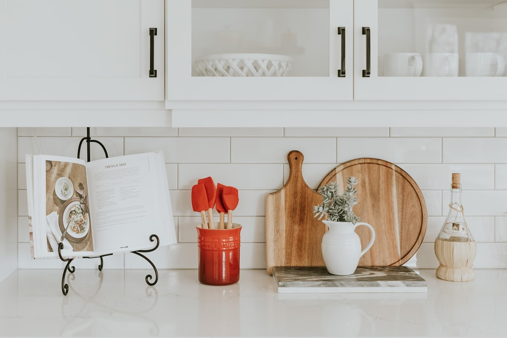 A white kitchen counter covered in misc. kitchen utensils. A cookbook is open on a book stand next to a red container.