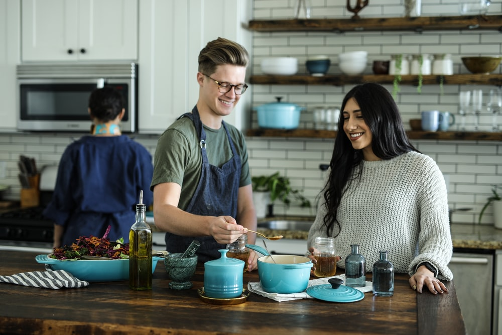 smiling man standing and mixing near woman in kitchen area of the house