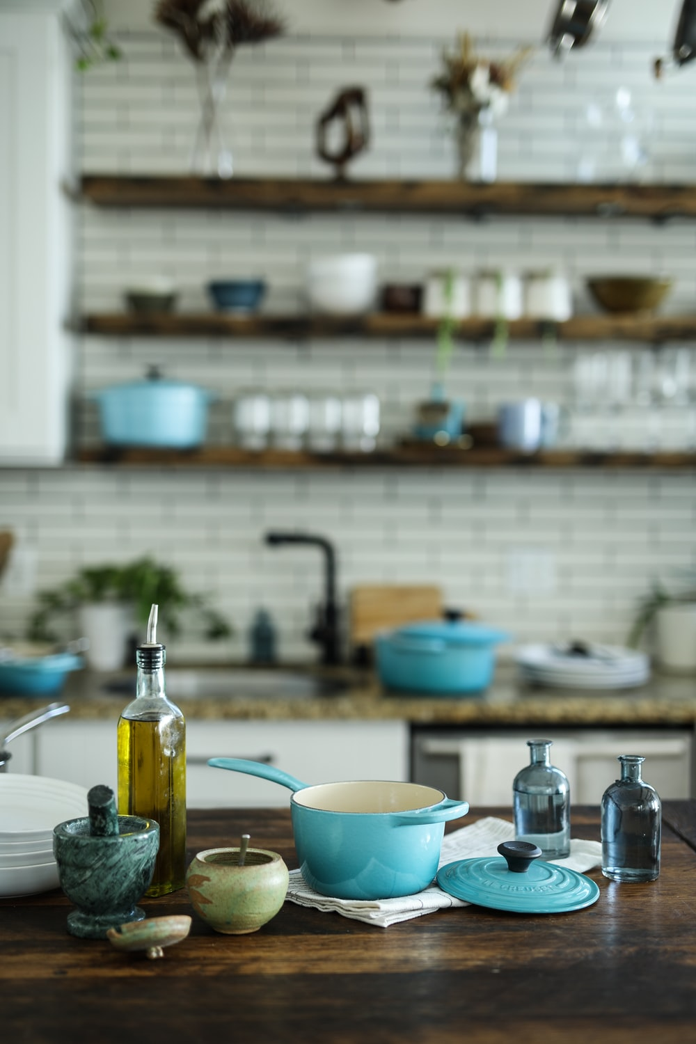 blue and white casserole near olive oil bottle on table
