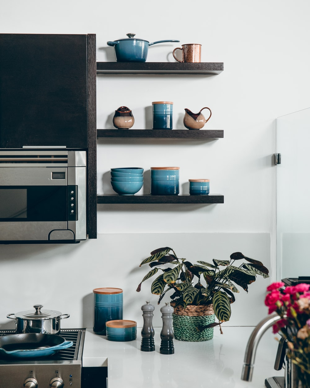 microwave beside containers on floating shelves