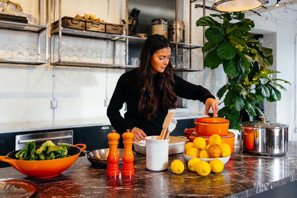 woman standing in front of fruits holding pot's lid