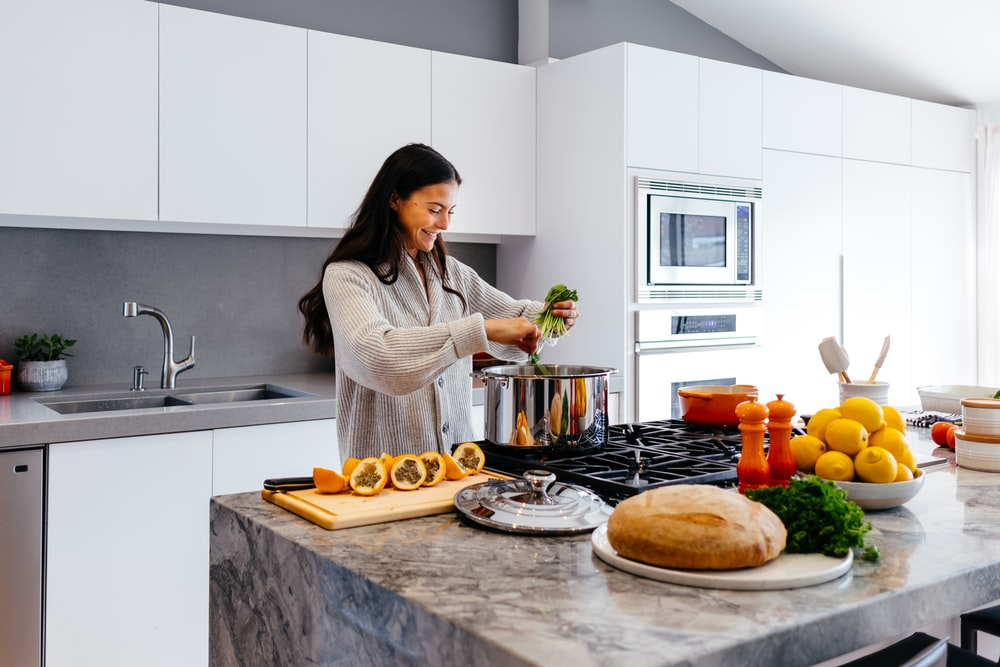 woman smiling while cooking