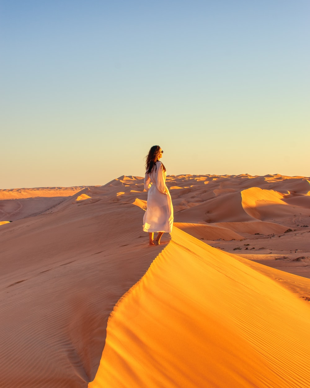 woman in white dress standing on desert mountain