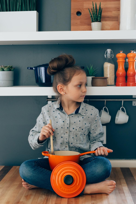 woman wearing grey blouse holding orange sauce pan and brown ladle