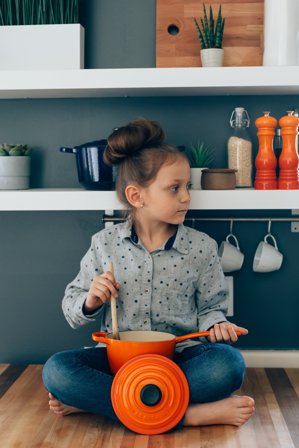 woman wearing grey blouse holding orange sauce pan and brown ladle