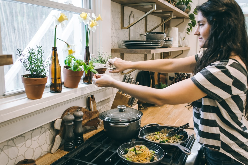woman standing in front of cooking range holding flower's leaves