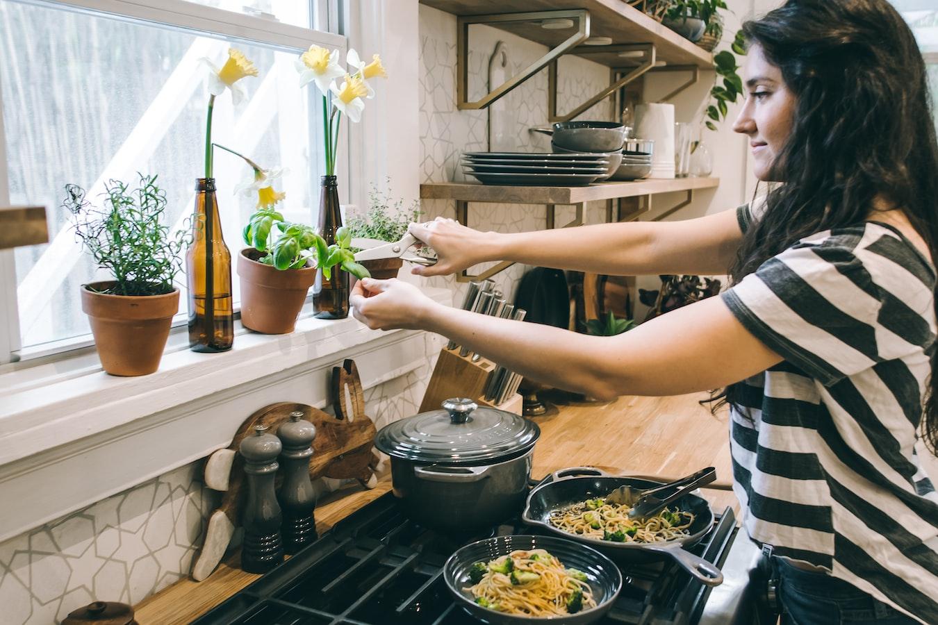 Frau kocht in einer Küche am Herd ein Nudelgericht