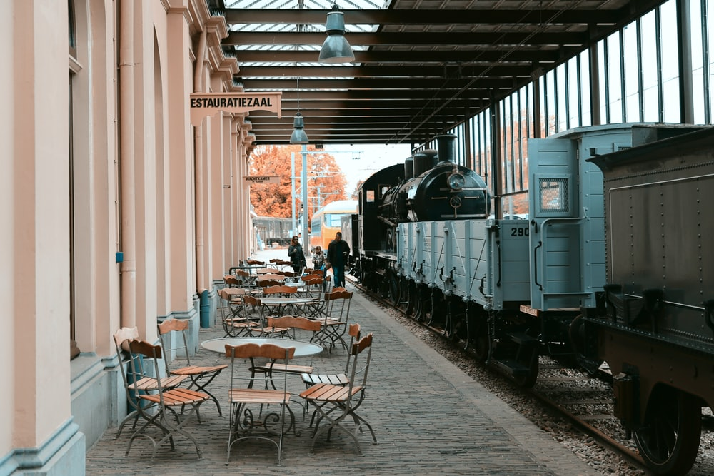 three people walking in alley with cafes and parked train