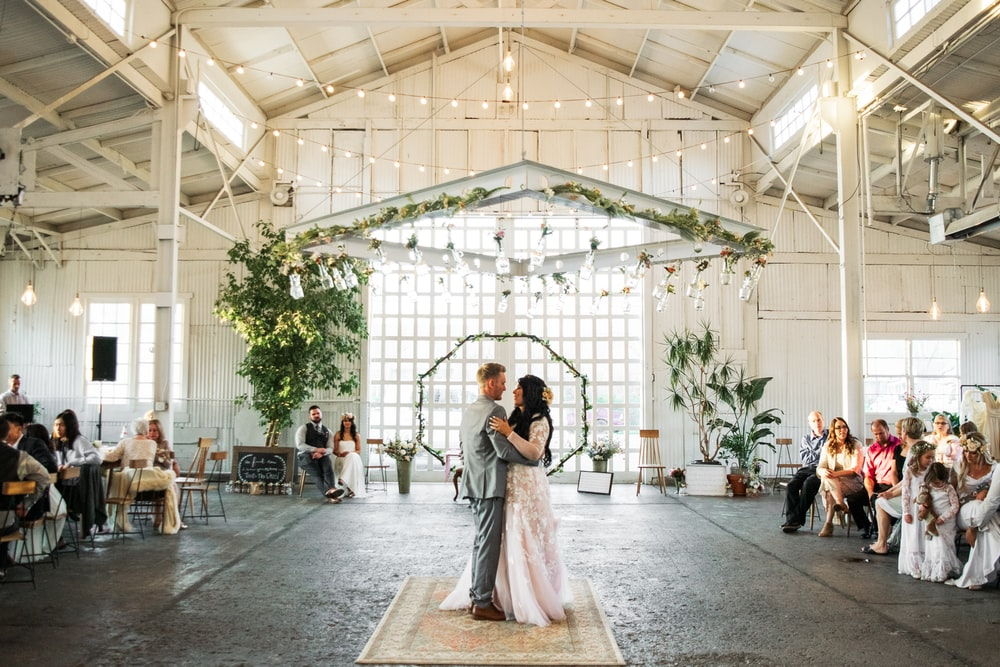 groom and bridge dancing inside building during daytime