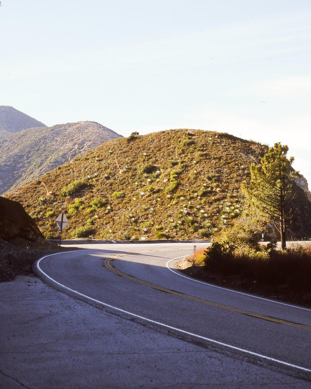 gray concrete road near hill