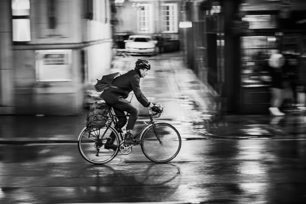 man riding bicycle on road during nighttime