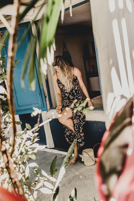 woman wearing floral dress sitting on window