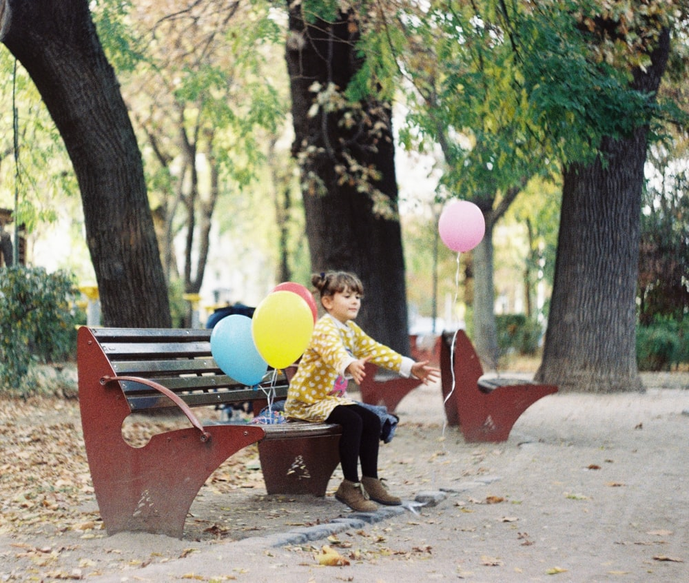 girl sitting on brown wooden bench during daytime