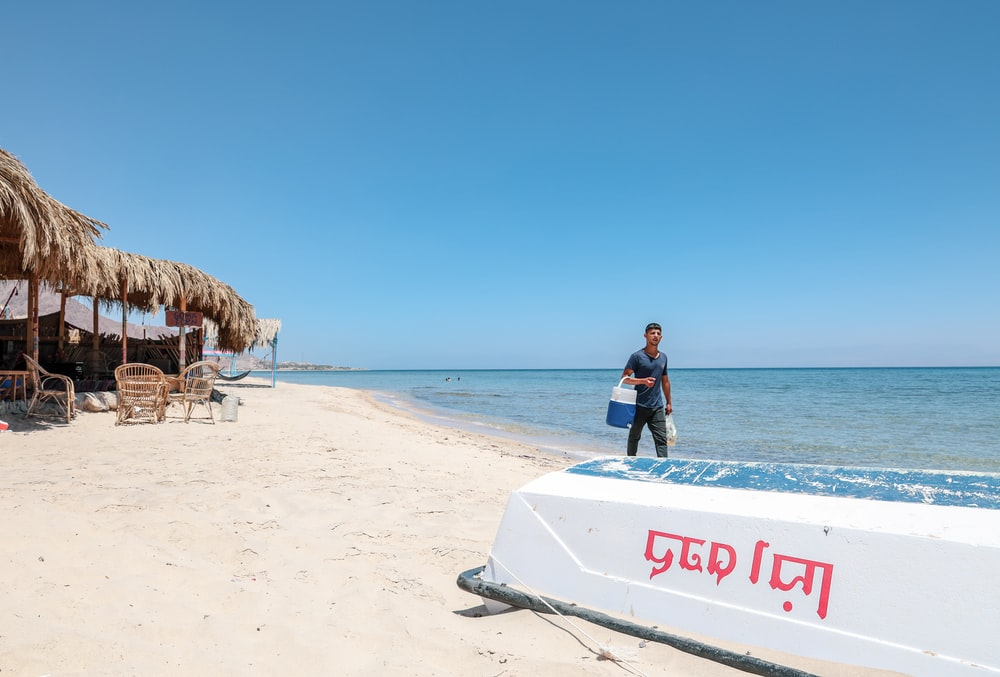 man carrying white and blue insulated beverage cooler in seashore