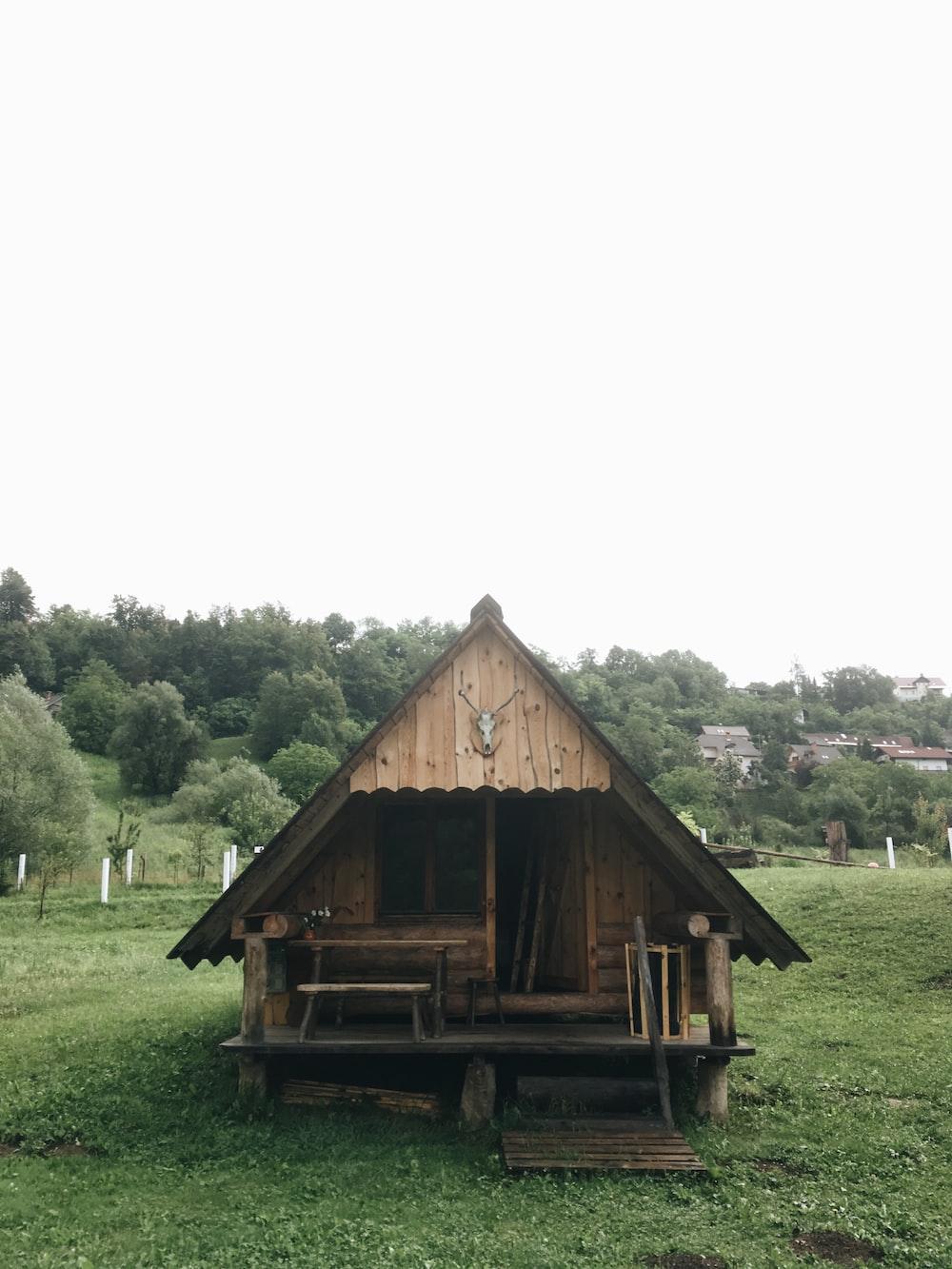 brown wooden house on green grassland during daytime
