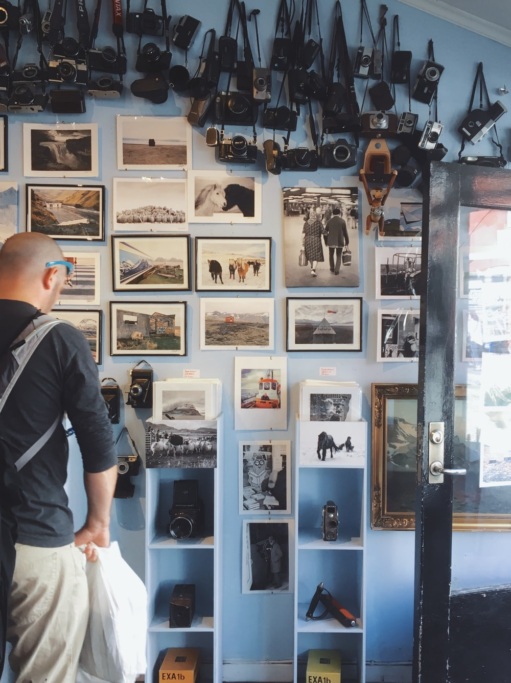 person wearing black long-sleeved shirt standing in front of assorted photos
