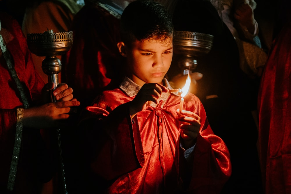 boy holding lighted candle