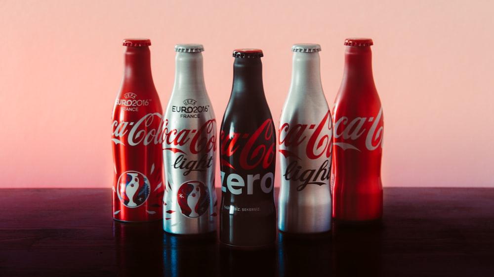 five assorted-color Coca-Cola bottles
