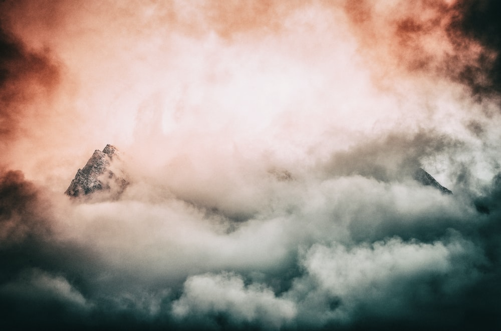 photography of mountain covered by clouds