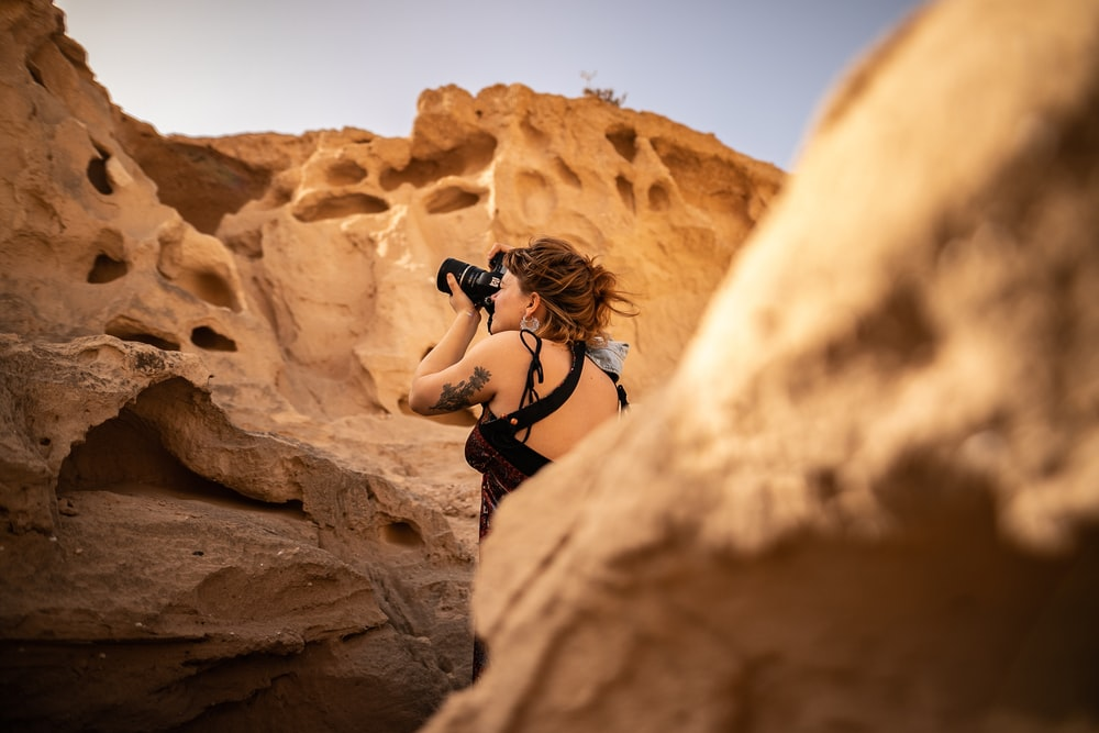 photography of woman standing near rock formation while taking photo during daytime
