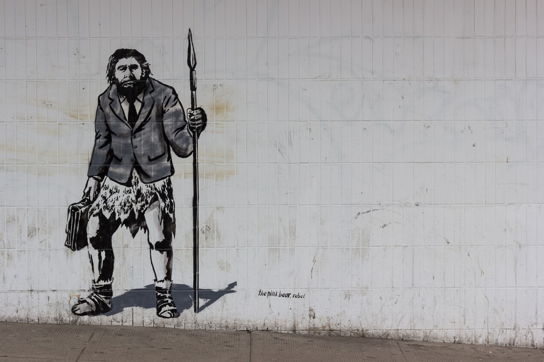 Lovely stencil work by thepinkbear.rebel street artist of a neanderthal man holding a briefcase in one hand and a spear in the other. Wearing a shirt, tie and suit jacket over an animal skin. Ready for a solid days work.