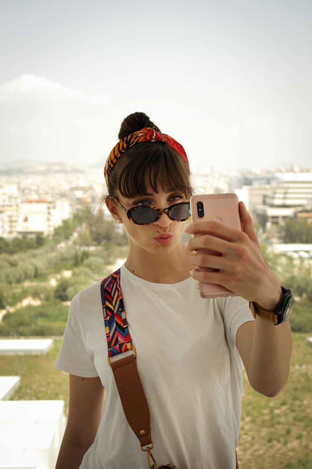 woman pouting her lips while holding smartphone in front of her face