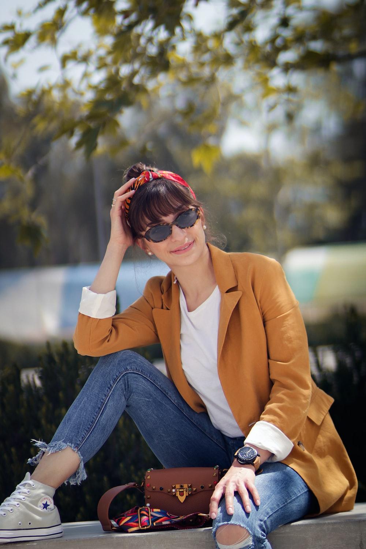 woman sitting on concrete bench near tree