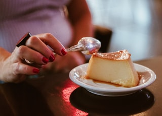 person holding spoon about to slice dessert
