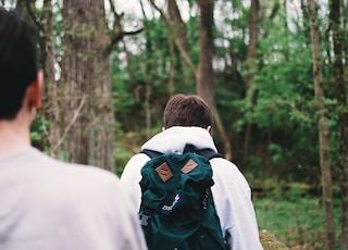 two men walking near trees