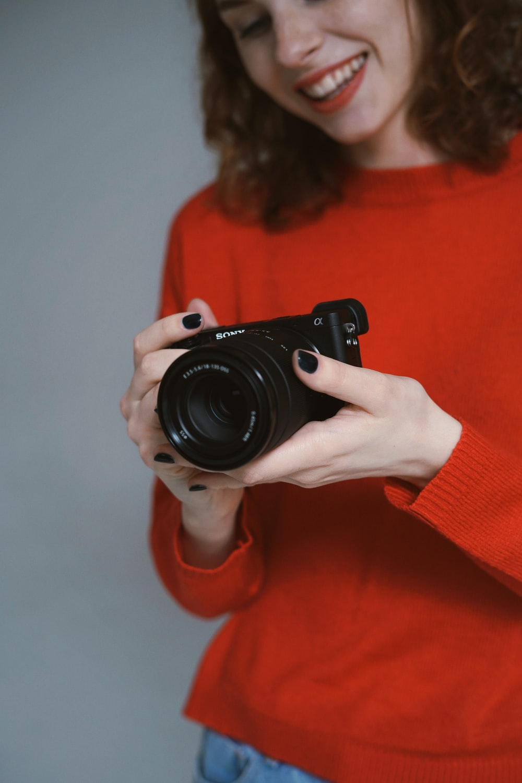 woman holding black DSLR cmaera