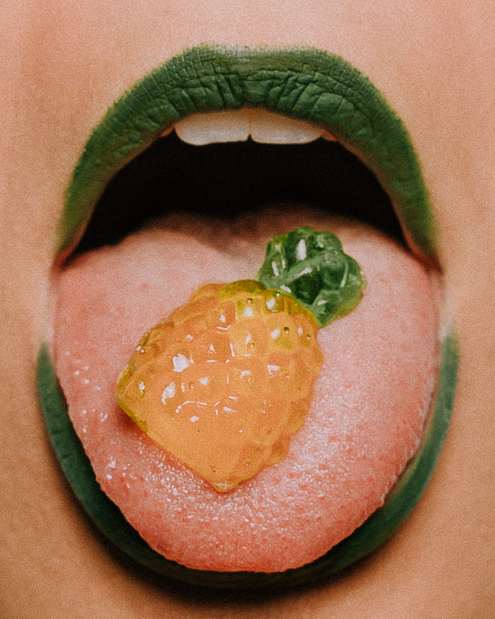 person showing tongue with pineapple candy