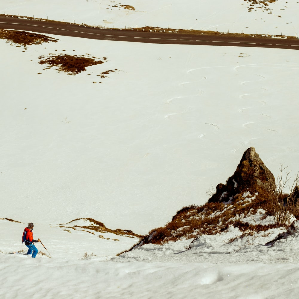 man walking on ice covered field during daytime