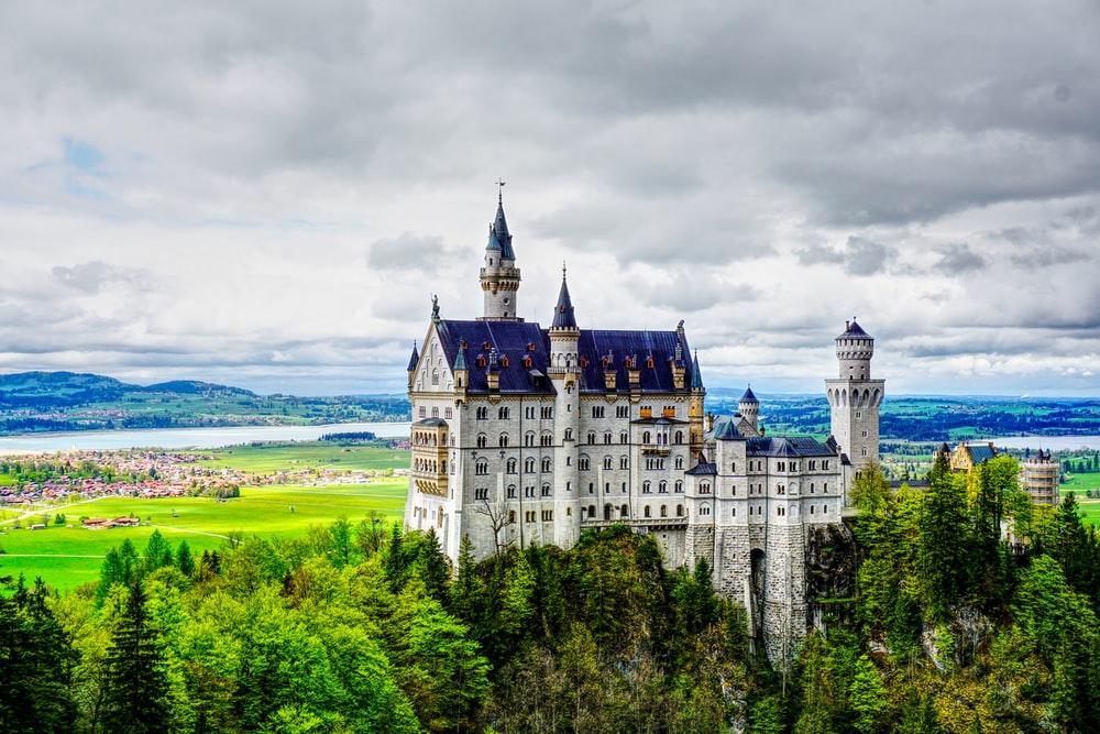 white and blue castle under gray clouds