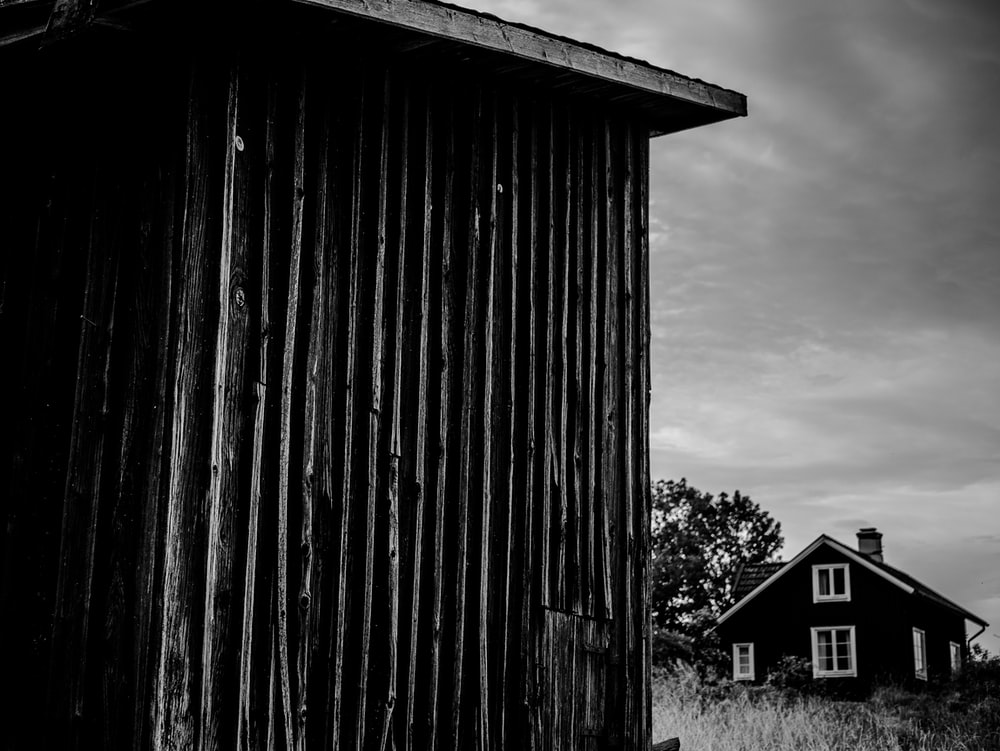 grayscale photo of house near shed