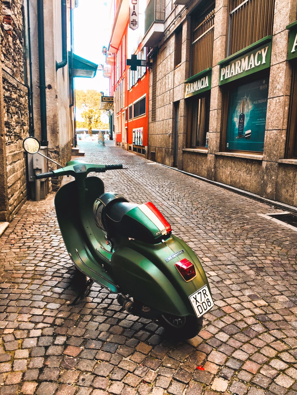 green motor scooter parked beside building