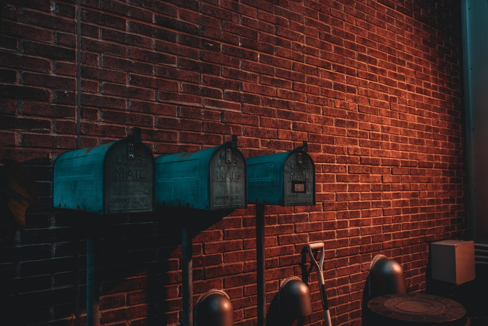 three green mail boxes near wall