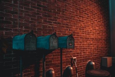 three green mail boxes near wall