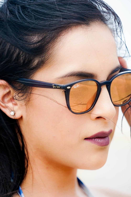 woman in black framed gold lens Ray-Ban wayfarer