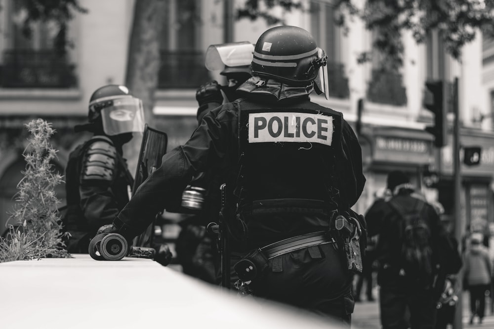grayscale photo of Police standing and leaning on wall