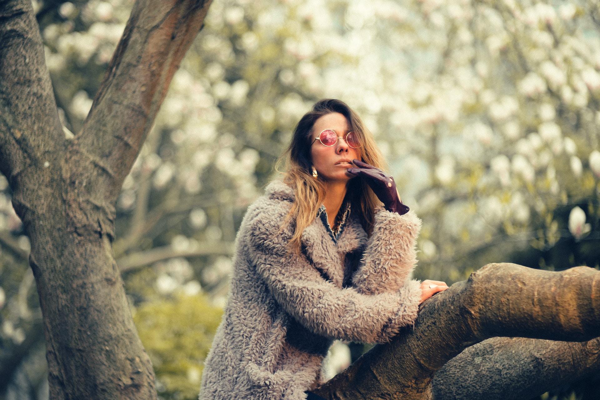 woman in gray coat sitting on tree stem