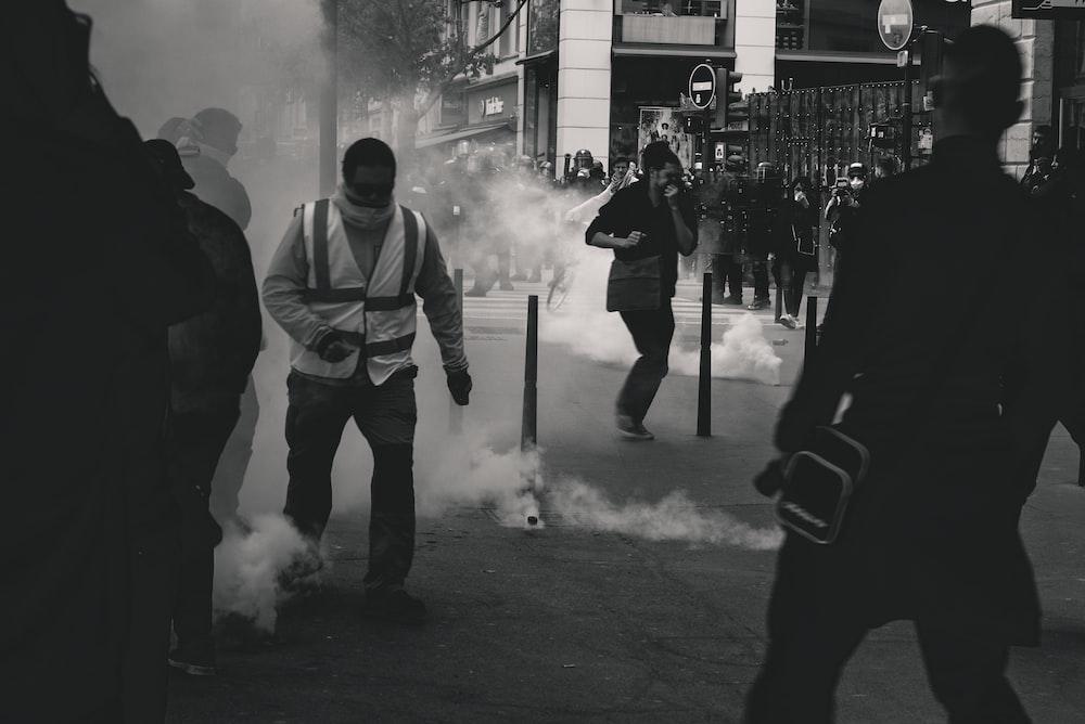 grayscale photo of people near smoke