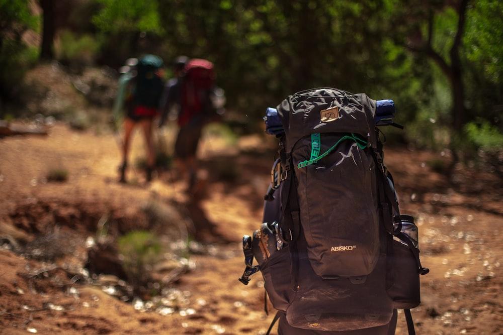 man carrying black hiking bag